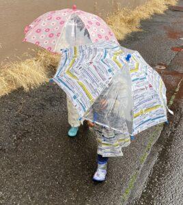 雨の日に傘をさす双子